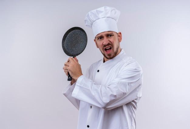 Professionele mannelijke chef-kok in wit uniform en kokhoed die een koekenpan met agressieve uitdrukking slingert die zich over witte achtergrond bevinden