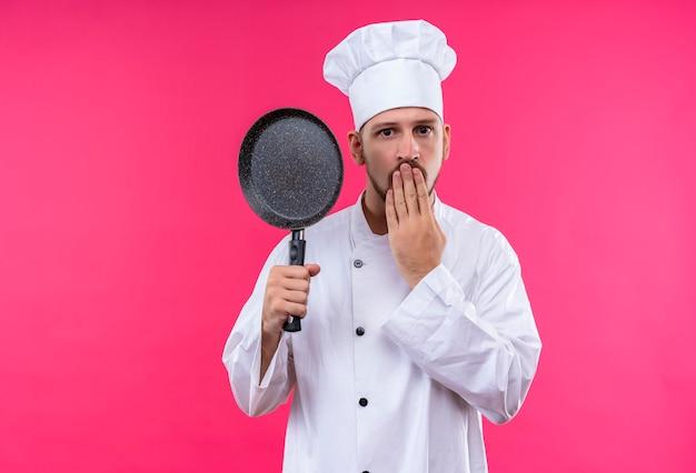 Professionele mannelijke chef-kok in wit uniform en kokhoed die een pan houdt die verbaasd kijkt die mond behandelt met hand die zich over roze achtergrond bevindt
