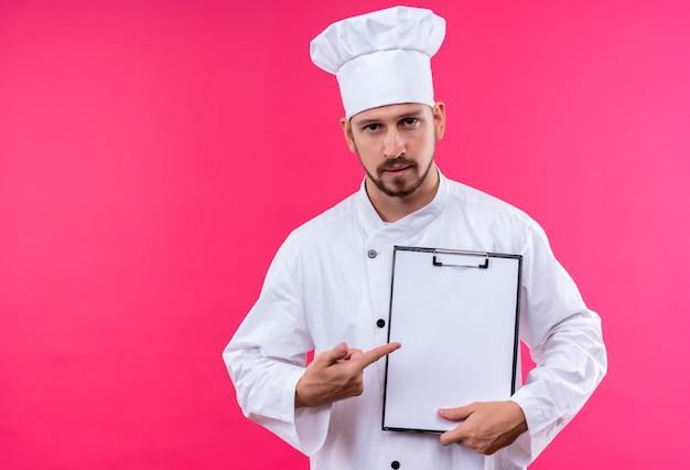 Professionele mannelijke chef-kok in wit uniform en kokhoed die klembord met blanco pagina's presenteert die zich over roze achtergrond bevinden