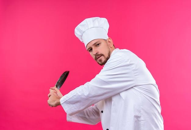 Professionele mannelijke chef-kok in wit uniform en kokhoed die met een keukenmes slingert dat zich over roze achtergrond bevindt