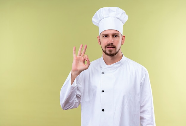 Professionele mannelijke chef-kok in wit uniform en kokhoed die ok gebaar toont die zich zeker over groene achtergrond bevinden kijkt