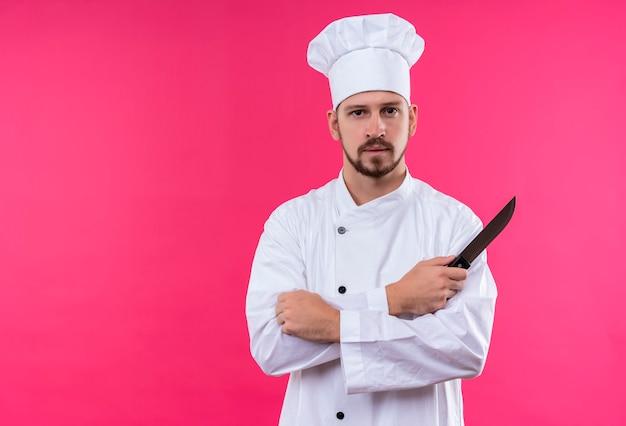 Professionele mannelijke chef-kok in wit uniform en kokhoed die zich met gekruiste wapens bevindt die een keukenmes houden die zelfverzekerd over roze achtergrond kijken Gratis Foto
