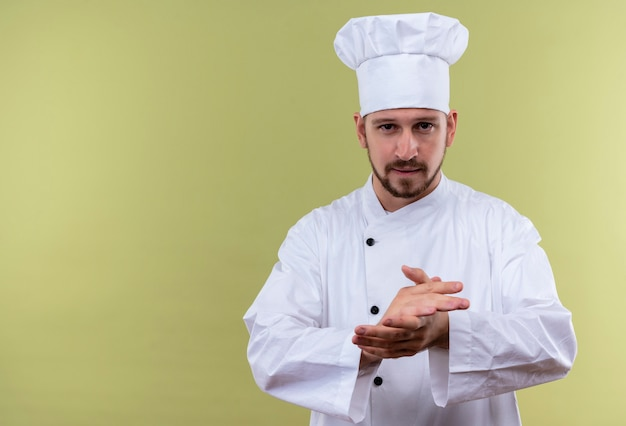Professionele mannelijke chef-kok in wit uniform en kokhoed die zijn handen wrijft op zoek zelfverzekerd, klaar om te koken staande over groene achtergrond