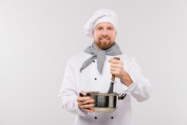 Professionele mannelijke chef-kok soep of andere maaltijd in de pan mengen tijdens het koken van voedsel voor camera geïsoleerd