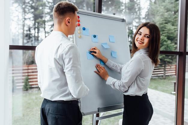 Professionele mannelijke en vrouwelijke zakenpartners die elkaar ontmoeten om de planningsstrategie voor een gemeenschappelijk startproject te bespreken