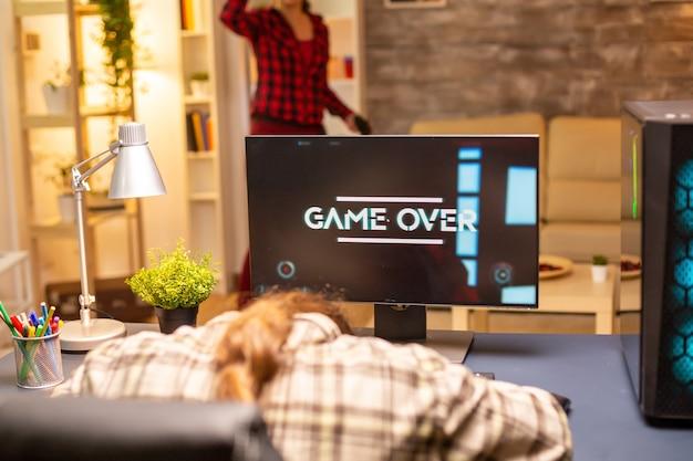 Professionele mannelijke gamer die op een krachtige pc speelt en het spel 's avonds laat in de woonkamer verliest