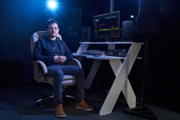 Professionele mannelijke geluidstechnicus mixen van audio in opnamestudio. muziekproductietechnologie, bezig met mixer