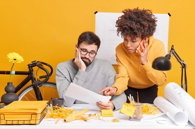 Professionele mannelijke ingenieur kijkt droevig naar papier luistert uitleg van vrouwelijke stagiair die via smartphone praat samen in coworking space. bouwvakkers werken aan technische plannen