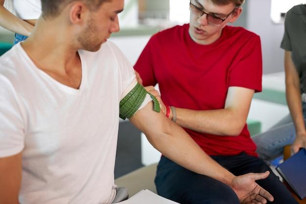 Professionele mannelijke instructeur die tourniquet gebruikt om bloeding te voorkomen tijdens ehbo-training