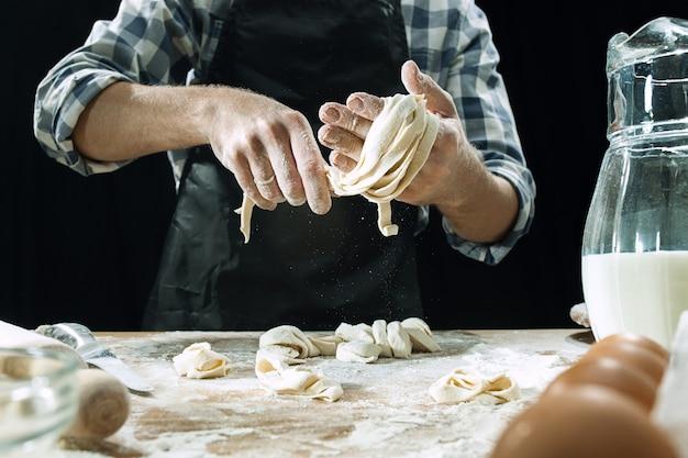 Professionele mannelijke kok bestrooit deeg met bloem, preapares of bakt brood aan de keukentafel