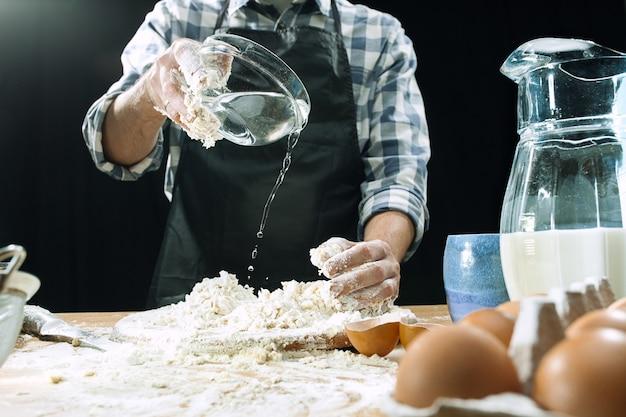 Professionele mannelijke kok bestrooit deeg met bloem, preapares of bakt brood of pasta aan de keukentafel, heeft vuile uniform, geïsoleerd op zwart krijt achtergrond. bakken concept