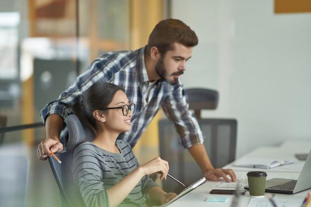 Professionele mannelijke mentor of leraar die computerwerk uitlegt aan jonge aziatische vrouwelijke stagiaire terwijl