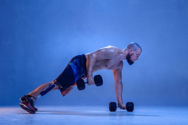 Professionele mannelijke sportman met beenprothese training met dumbbells