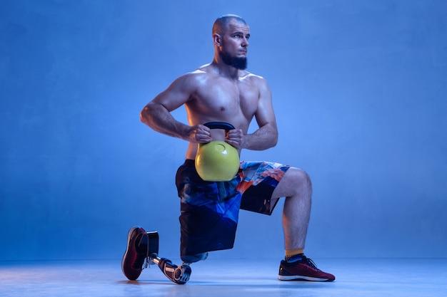 Professionele mannelijke sportman met beenprothese training met kettlebell