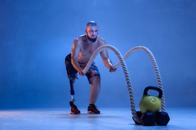 Professionele mannelijke sportman met beenprothese training met touwen in neon Premium Foto