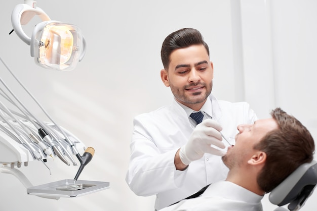 Professionele mannelijke tandarts die met zijn patiënt werkt die zijn tanden onderzoekt