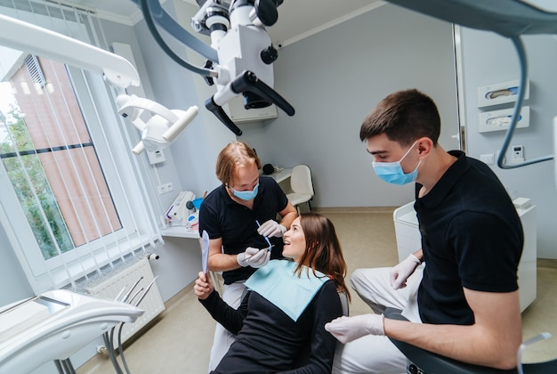 Professionele mannelijke tandartsen die moderne technologieën gebruiken bij tandheelkundige behandelingen, gecompliceerde gevallen in de stomatologie. mondzorgconcept