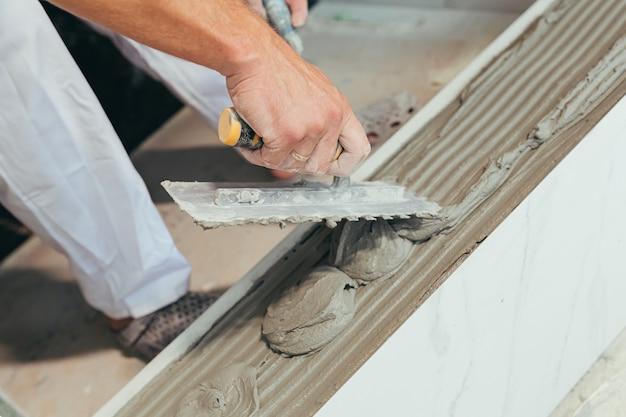 Professionele mannelijke werknemer monteert keramische tegels in badkamerfoto met dichte spatel met lijm