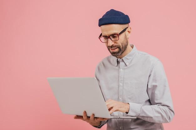 Professionele mannelijke werknemer zoekt naar interessante film om te bekijken, gebruikt gadget, typt informatie op laptopcomputer