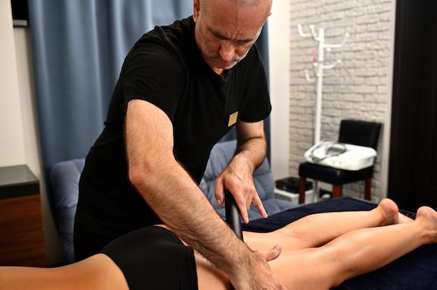 Professionele massagetherapeut, chiropractor die thaise massage uitvoert in kuuroord met bamboestok. lichaamsverjongende, lichaamsverzorgingsconcepten