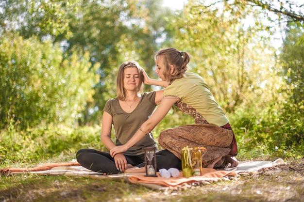 Professionele masseuse past haar massagevaardigheden toe op haar cliënt bij daglicht.