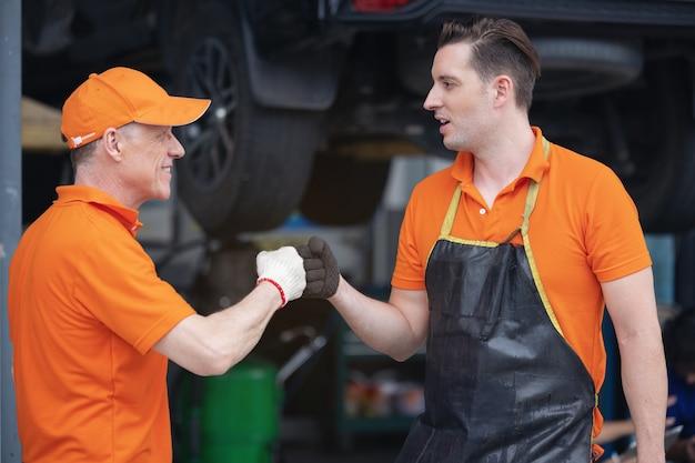 Professionele mechanische medewerker van de autoservice-handdruk voor eens en beiden zien er gelukkig en tevreden uit