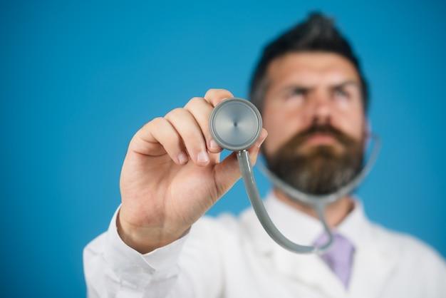 Professionele medische bebaarde arts met stethoscoop in de hand arts houdt in zijn hand stethoscoop