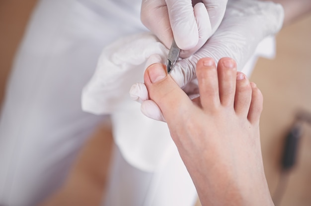 Professionele medische pedicure procedure close-up met nagelknipper