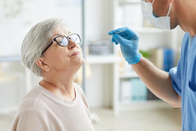Professionele medische werker dragen persoonlijke beschermingsmiddelen senior vrouw testen op aandoeningen van de luchtwegen met behulp van teststok