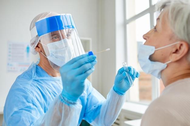 Professionele medische werker dragen persoonlijke beschermingsmiddelen senior vrouw testen op gevaarlijke ziekte met behulp van teststok