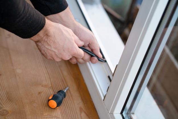 Professionele meester in reparatie en installatie van ramen, verandert rubberen afdichtingspakking in pvc-ramen