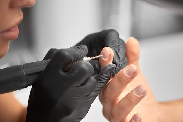 Professionele meester manicure bezig met de vingernagels van de cliënt