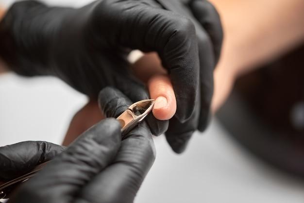 Professionele meester manicure bezig met de vingernagels van de klant