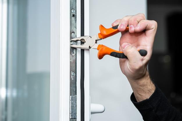 Professionele meester voor reparatie en installatie van ramen, zet een raamopeningssysteem op in de wintermodus