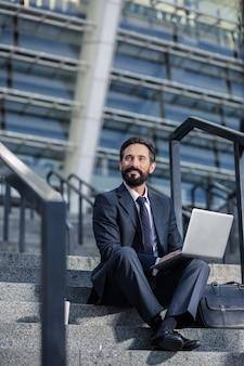 Professionele mentaliteit. aangename bebaarde zakenman met zijn laptop op de trappen