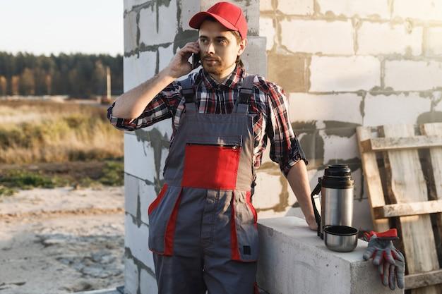 Professionele metselaar praten door smartphone op de bouwplaats