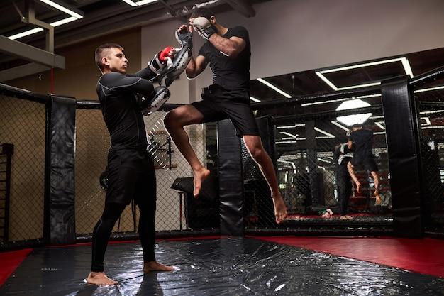 Professionele mma-jager leert zelfverdedigingstrucs en laat het aan jonge bokser zien. samen verschillende technieken oefenen. sport, trainingsconcept. kopieerruimte zijaanzicht