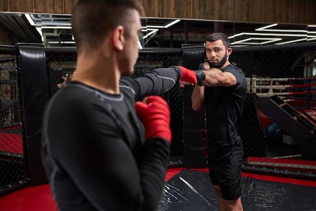 Professionele mma-vechter die de beste trucs toont aan nieuwe vechter, lesgeeft, samen traint, bezig is met training, masterclass door professionele mma-worstelaar. achteraanzicht