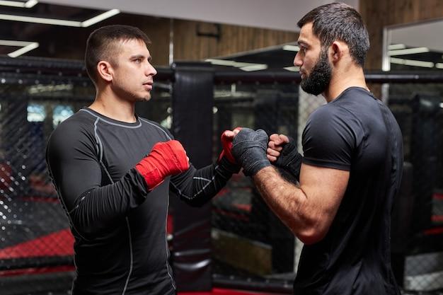 Professionele mma-vechter die de beste trucs toont aan nieuwe vechter, lesgeeft, samen traint, bezig is met training, masterclass door professionele mma-worstelaar