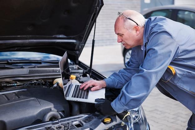 Professionele monteur die op het werk moderne technologie gebruikt