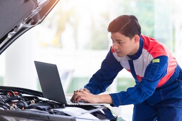 Professionele monteur in uniform is controleer de kwaliteit van de motorolie van nieuwe auto's voordat deze aan klanten wordt geleverd. tijdens het werken in een autoreparatiecentrum door een laptop als werkinstrument te gebruiken.