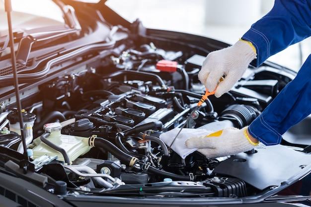 Professionele monteur in uniform is controleer de kwaliteit van de motorolie van nieuwe auto's voordat deze aan klanten wordt geleverd. tijdens het werken in een autoreparatiecentrum.