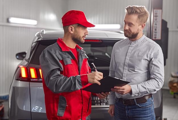 Professionele monteur maken van aantekeningen in controlelijstdocument tijdens bespreking van autoreparatie met mannelijke cliënt in moderne werkplaats