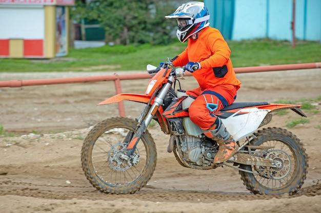 Professionele motorcross motorrijder rijdt over de wegbaan