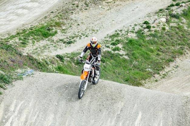 Professionele motorcrosser rijdt over de weg