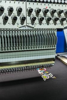 Professionele naaimachine borduurwerk kleurenpatroon, close-up. textielstof, niemand. fabrieksproductie, naaiproductie, handwerktechnologie