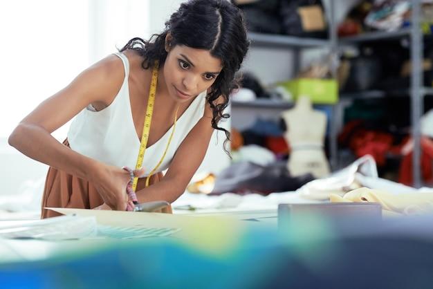 Professionele naaister naaien jurk in haar atelier voor klant
