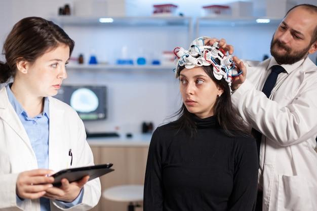 Professionele neurologische onderzoeker die het behandelresultaat uitlegt terwijl hij op de monitor wijst terwijl de medische wetenschapper de eeg-headset aanpast, zich voorbereidt op de hersenscan die elektrische activiteit analyseert, het zenuwstelsel