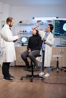 Professionele neurologische onderzoeker die het behandelresultaat uitlegt terwijl medisch wetenschapper de eeg-headset aanpast en zich voorbereidt op hersenscan die elektrische activiteit, zenuwstelsel analyseert