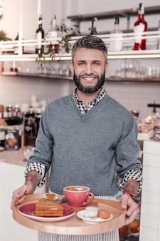 Professionele ober. opgetogen vrolijke man die met een dienblad aan het werk was als professionele ober